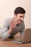 Jeune homme gai se trouvant sur le plancher avec l'ordinateur portable Photos stock