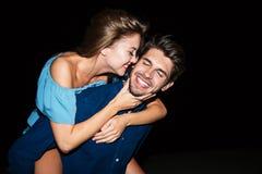 Jeune homme gai tenant l'amie sur le sien de retour la nuit image libre de droits