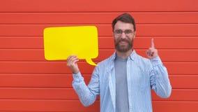 Jeune homme gai tenant un nuage de dialogue ou un discours jaune rectangulaire de bulle sur le fond rouge banque de vidéos