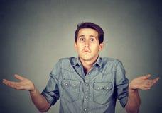 Jeune homme gesticulant des épaules qui s'inquiète ainsi ce qui le don& x27 d'I ; t savent image stock