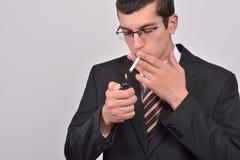 Jeune homme habillé en cigarette d'éclairage de smoking Photos stock