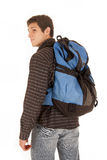 Jeune homme habillé occasionnel avec le sac à dos bleu regardant au-dessus du shoulde Image libre de droits