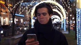 Jeune homme habillé occasionnel passant en revue son téléphone portable sur une rue urbaine occupée la nuit banque de vidéos