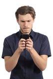 Jeune homme hanté avec son téléphone intelligent Photographie stock libre de droits