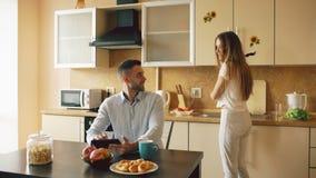 Jeune homme heureux à l'aide de la tablette numérique se reposant dans la cuisine et parlant son épouse tandis qu'elle faisant cu Photo stock