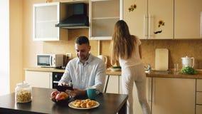Jeune homme heureux à l'aide de la tablette numérique se reposant dans la cuisine et parlant son épouse tandis qu'elle faisant cu Images libres de droits