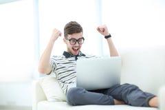 Jeune homme heureux à l'aide de son ordinateur portable dans le salon lumineux Photo stock
