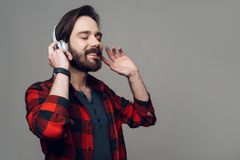 Jeune homme heureux écoutant la musique avec des écouteurs photographie stock