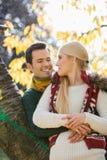 Jeune homme heureux étreignant la femme tout en se penchant sur le tronc d'arbre pendant l'automne en parc Photo stock