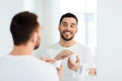 Jeune homme heureux appliquant la crème au visage à la salle de bains Images libres de droits