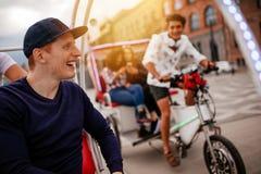Jeune homme heureux appréciant le tour de tricycle avec des amis Photographie stock libre de droits