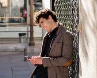 Jeune homme heureux attirant de hippie parlant au t?l?phone intelligent dans la ville europ?enne images libres de droits