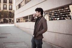 Jeune homme heureux attirant parlant au t?l?phone intelligent dans la ville europ?enne photos libres de droits