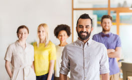 Jeune homme heureux au-dessus d'équipe créative dans le bureau Image stock