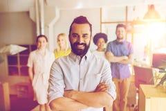 Jeune homme heureux au-dessus d'équipe créative dans le bureau Photo libre de droits