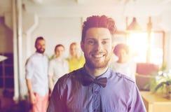 Jeune homme heureux au-dessus d'équipe créative dans le bureau Images stock