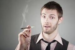 Jeune homme heureux avec le petit cigare Image stock