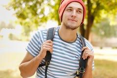 Jeune homme heureux avec le sac à dos augmentant en bois Images stock