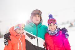 Jeune homme heureux avec les amis féminins tenant le bras autour dans la neige Image stock