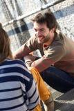 Jeune homme heureux ayant une conversation avec la femme Photo stock