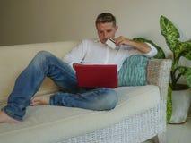 Jeune homme heureux beau et attirant faisant des achats d'Internet réfléchis en ligne avec la carte de crédit reposant à la maiso photographie stock libre de droits