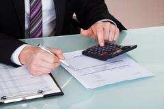 Jeune homme heureux calculant des finances Photos libres de droits