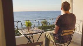 Jeune homme heureux détendant sur la terrasse d'hôtel de luxe banque de vidéos