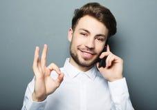 Jeune homme heureux d'affaires dans la chemise faisant des gestes et souriant tandis que t Photographie stock libre de droits