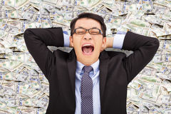 Jeune homme heureux d'affaires se trouvant sur dollar US Photo libre de droits
