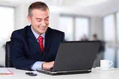 Jeune homme heureux d'affaires travaillant au carnet Image stock