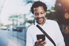 Jeune homme heureux d'Afro-américain dans l'écouteur marchant à la ville ensoleillée et faisant la conversation visuelle avec des Photos libres de droits