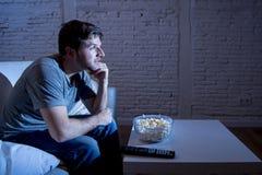 Jeune homme heureux d'intoxiqué de télévision s'asseyant sur le sofa à la maison regardant la TV et mangeant du maïs éclaté Photo libre de droits