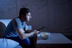 Jeune homme heureux d'intoxiqué de télévision s'asseyant sur le sofa à la maison regardant la TV manger du maïs éclaté Photos libres de droits
