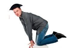 Jeune homme heureux dans le capuchon de graduation Image stock