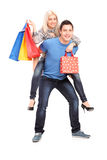 Jeune homme heureux donnant un tour de ferroutage à son amie avec s Image stock