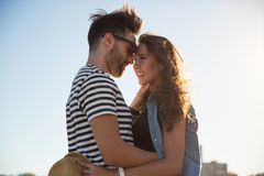 Jeune homme heureux embrassant son amie dehors Photographie stock