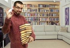 Jeune homme heureux en verres avec les livres à la bibliothèque images stock