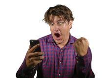 Jeune homme heureux et enthousiaste fol c?l?brant le succ?s gagnant l'argent jouant en ligne avec le pari de gain d'Internet de t photos stock
