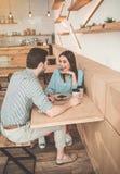 Jeune homme heureux et femme parlant en café Photos stock