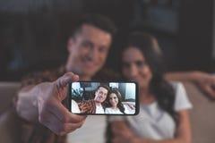 Jeune homme heureux et femme prenant la photo au téléphone photographie stock