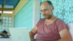 Jeune homme heureux et sûr de randonneur travaillant avec l'ordinateur portable et la mise en réseau en tant que l'entrepreneur i photographie stock libre de droits