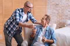Jeune homme heureux faisant la proposition à son associé âgé Images stock