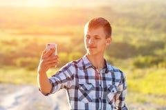 Jeune homme heureux faisant un selfie au téléphone et souriant, fond naturel à la lumière du soleil photos stock