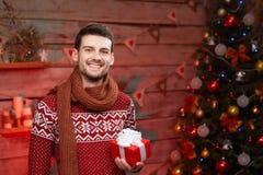 Jeune homme heureux jugeant présent dans le temps de Noël Photo stock