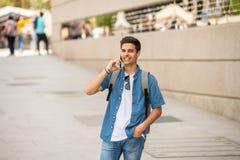 Jeune homme heureux moderne beau parlant à son téléphone intelligent dehors dans la ville image libre de droits