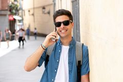 Jeune homme heureux moderne beau parlant à son téléphone intelligent dehors dans la ville images libres de droits
