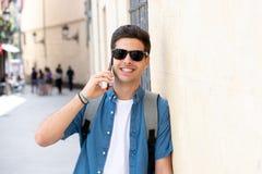 Jeune homme heureux moderne beau parlant à son téléphone intelligent dehors dans la ville photos stock