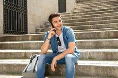 Jeune homme heureux moderne beau parlant à son téléphone intelligent dehors dans la ville photo stock