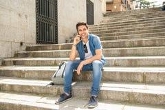 Jeune homme heureux moderne beau parlant à son téléphone intelligent dehors dans la ville image stock