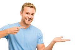 Jeune homme heureux montrant le copyspace vide sur le fond blanc Photo libre de droits